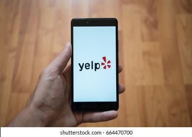 London, United Kingdom, june 5, 2017: Man holding smartphone with Yelp logo on the screen. Laminate wood background.