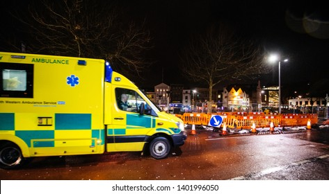 London, United Kingdom - Mar 5, 2017: Defocused Yellow NHS ambulance driving fast on the repaired with roadworks street in central london at night