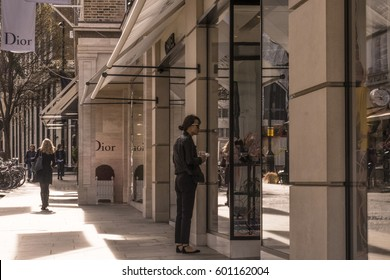 LONDON, UNITED KINGDOM - MARCH 13, 2017: Woman looking at window display of Chanel in New Bond Street, with Dior sign behind.