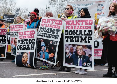 London / United Kingdom - March 16 2019:  Women at an anti-racism rally holding up banners in protest of politicians known for making divisive, racist remarks