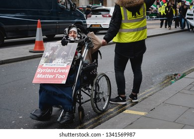London / United Kingdom - March 16 2019: At a Syrian solidarity march, a woman in a wheelchair is assisted by a fellow rally-goer whilst holding up a sign in protest against the Assad regime