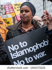 London / United Kingdom - March 16 2019: A muslim woman holds up an anti racism, anti war sign at a rally