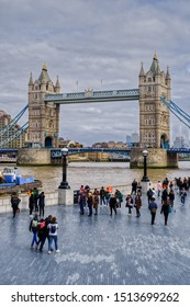 London, United Kingdom - March 23 2019: People walking on weekend with Tower Bridge, Thames river and boats in background. HDR shot in daylight, cloudy sky. Capturing a hug between friends.