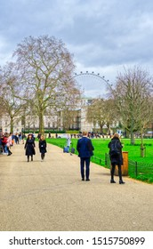 London, United Kingdom - March 23 2019: London Eye from a park in spring. HDR shot to enhance the details, people relaxing enjoying the weekend. Green grass and trees with red leaves. Cloudy sky.