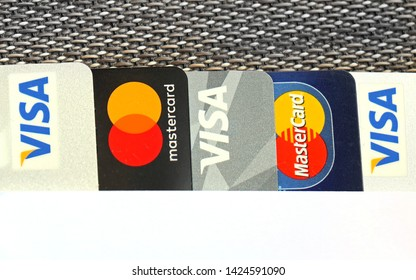 London, United Kingdom - May 10, 2019: Pile of different credit and debit bank cards arranged in a row on flat surface. Cards are from multinational financial services Visa and Mastercard.