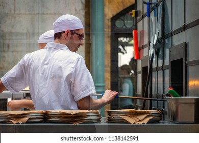 LONDON, UNITED KINGDOM - MAY 12 2018: Unidentified chef bakes plate of pizzas in an Italian restaurant at Covent Garden Market