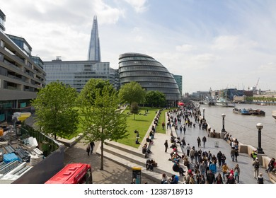 LONDON, UNITED KINGDOM  - MAY 15, 2015 - The Southbank with many people walking with City Hall and The Shard in the background