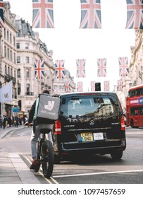 LONDON, UNITED KINGDOM - MAY 18, 2018: Vintage filter over Deliveroo cyclist waiting at red light near taxi on Regent Street with flags celebrating Meghan Markle Prince Harry marriage