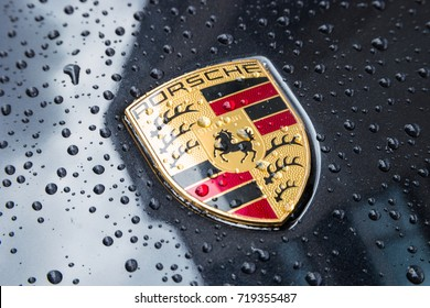 LONDON, UNITED KINGDOM MAY, 2017: Porsche Logo Close Up on a black car with rain drops. Ferdinand Porsche founded the company in 1931 with main offices in the centre of Stuttgart.