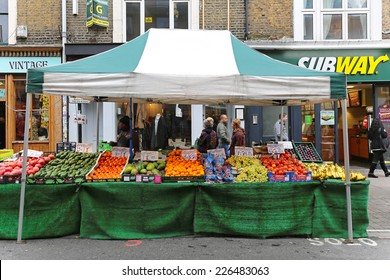 LONDON, UNITED KINGDOM - NOVEMBER 24: Brick Lane Market in East London on NOVEMBER 24, 2013. Temporary street market stall with fruits and vegetables on Sunday in London, United Kingdom.