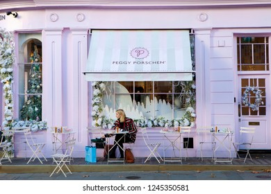 LONDON, UNITED KINGDOM - NOVEMBER 30th, 2018: Young woman is sitting outside fashionable cake shop in stylish area of Chelsea.