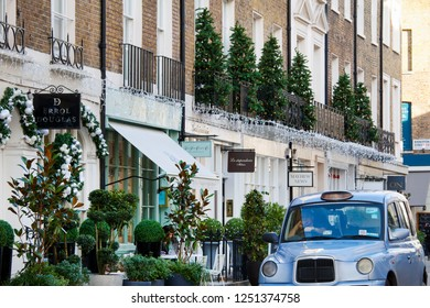 LONDON, UNITED KINGDOM - NOVEMBER 30th, 2018: Shops are decorated for Christmas on high street in elegant area of Belgravia in Central London