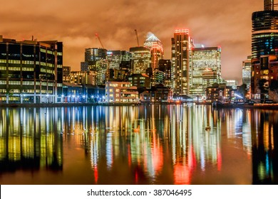 London, United Kingdom - October 06, 2015: Canary Wharf financial district at rainy night with colourful reflections shot from Millwall Dock