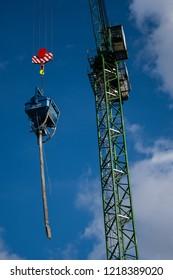 London, United Kingdom - October 18 2018:   A Crane lifts a cement hopper and hose into a blue sky  near Elizabeth Street