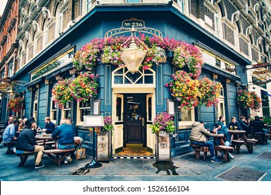 LONDON, UNITED KINGDOM - October 2019: Old traditional English Pub , Brewery, Pub entrance decorated with flowers in Central London, United Kingdom