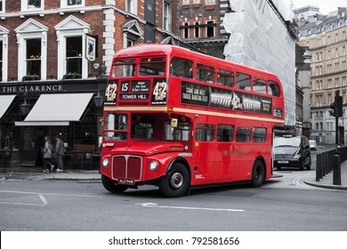 London, United Kingdom - October 21, 2017: Red double-decker bus goes on the street, one of the most popular symbols of the city. Ordinary people walk sidewalks
