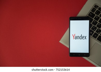 London, United Kingdom, October 23, 2017: Yandex logo on smartphone screen placed on laptop keyboard. Empty place to write information with red background.