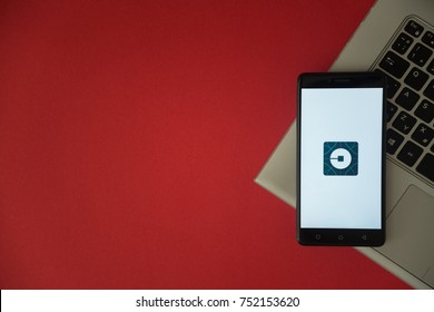 London, United Kingdom, October 23, 2017: Uber logo on smartphone screen placed on laptop keyboard. Empty place to write information with red background.