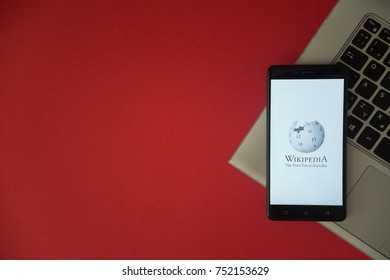 London, United Kingdom, October 23, 2017: Wikipedia logo on smartphone screen placed on laptop keyboard. Empty place to write information with red background.