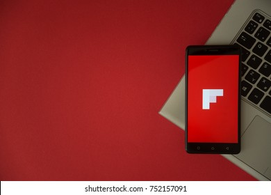 London, United Kingdom, October 23, 2017: Flipboard logo on smartphone screen placed on laptop keyboard. Empty place to write information with red background.