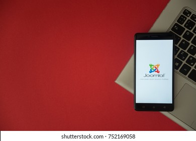 London, United Kingdom, October 23, 2017: Joomla logo on smartphone screen placed on laptop keyboard. Empty place to write information with red background.