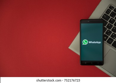 London, United Kingdom, October 23, 2017: Whatsapp logo on smartphone screen placed on laptop keyboard. Empty place to write information with red background.