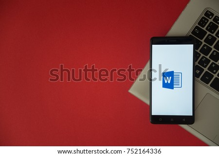 London, United Kingdom, October 23, 2017: Microsoft office word logo on smartphone screen placed on laptop keyboard. Empty place to write information with red background.