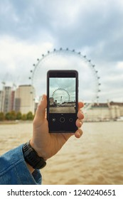 London, United Kingdom - October 26th 2018: Tourist with the cellphone, taking photo of the London Eye