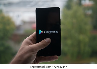 London, United Kingdom, october 3, 2017: Man holding smartphone with Google play store logo with the finger on the screen