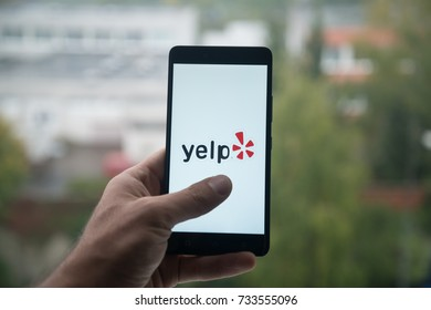 London, United Kingdom, october 3, 2017: Man holding smartphone with Yelp logo with the finger on the screen
