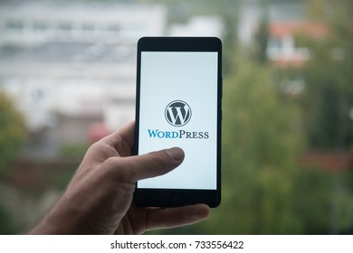 London, United Kingdom, october 3, 2017: Man holding smartphone with Wordpress logo with the finger on the screen