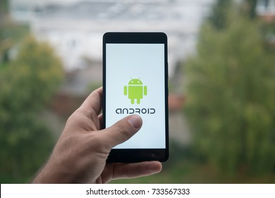 London, United Kingdom, october 3, 2017: Man holding smartphone with Android logo with the finger on the screen