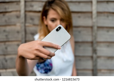 London, United Kingdom - October 30, 2018: Young girl makes selfie on new white iPhone smartphone. iPhone X, iPhone XS, iPhone XS Max.