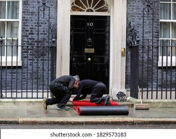 London / United Kingdom - October 8 2020: Number 10 staff lay a red carpet  at Downing Street ahead of an official welcoming.