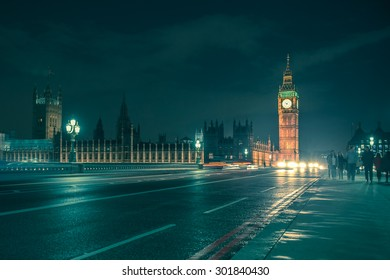 LONDON, UNITED KINGDOM - OCTOBER 9, 2014:  Night view of Big Ben across with Westminster Bridge on a damp night with cars and people crossing.