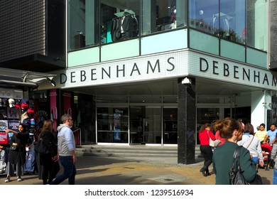 LONDON, UNITED KINGDOM - SEPTEMBER 10 2018: Debenhams store in Oxford Street in afternoon sun, with people walking past on the pavement/sidewalk wearing summer clothes. Two Debenhams logos can be seen