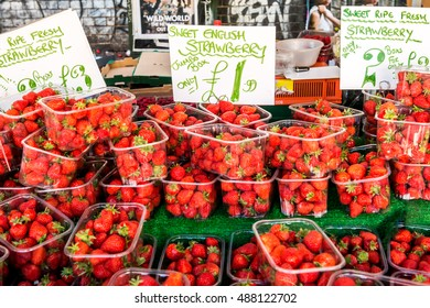 London, United Kingdom - September 11, 2016: Brick Lane street Sunday market - fruits and vegetables stall. Sweet British Strawberry sign