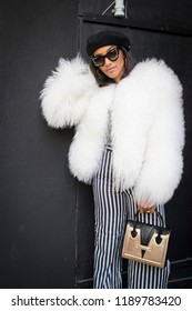 LONDON, United Kingdom- SEPTEMBER 14 2018: People on the street during the London Fashion Week. girl in a white fur coat, striped trousers and a black beret
