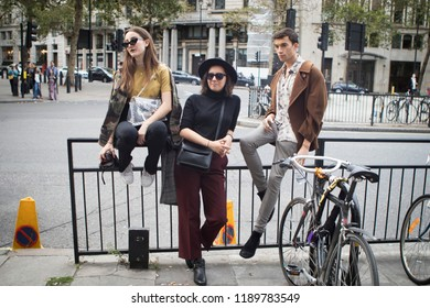 LONDON, United Kingdom- SEPTEMBER 14 2018: People on the street during the London Fashion Week. Three friends waiting.