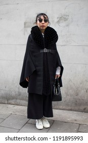 LONDON, United Kingdom- SEPTEMBER 14 2018: People on the street during the London Fashion Week. A woman in a black kimono coat with a belt and wearing sunglasses poses