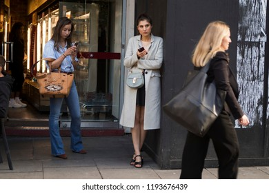 LONDON, United Kingdom- SEPTEMBER 14 2018: People on the street during the London Fashion Week. Two girls stand at the wall, look into your phone