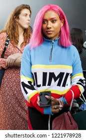 LONDON, United Kingdom- SEPTEMBER 14 2018: People on the street during the London Fashion Week. Girls with pink hair watch their phone. Eighties style clothing