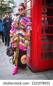 LONDON, United Kingdom- SEPTEMBER 14 2018: People on the street during the London Fashion Week. Girl in a multi-colored knitted cardigan