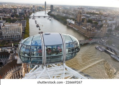London, United Kingdom - September 26: Tourists looking at landmark Big Ben out from a pod on the London Eye which was built to celebrate the millennium on September 26, 2014 in London, UK.