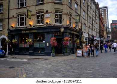 London, United Kingdom - September 7, 2019: The White Horse public house with many people outside some motion blurred and patrons inside