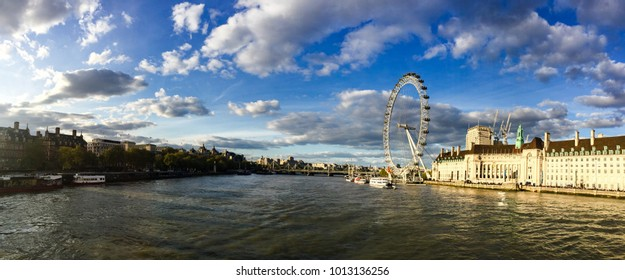 London, United Kingdom-April 15, 2017: London cityscape - London Eye with The Thames River in evening sunshine with white cloud on the bright blue sky in panorama view.