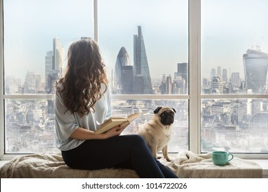 London view from window. Woman with dog sitting next to the window with book and enjoying amazing view