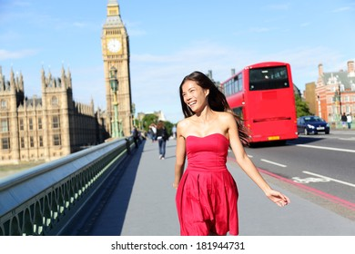 London woman happy walking by Big Ben, England. Tourist on Europe travel sightseeing running in joy by red double decker bus, Westminster Bridge, London, England