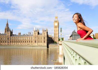 London woman on Westminster Bridge by Big Ben, England. Beautiful tourist girl sightseeing travel on Westminster Bridge, London, England, United Kingdom. Elegant multiracial female model in red dress.