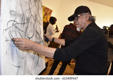 London-April 4 2017 : Malaysian painter and abstract expressionist performing a 'live' charcoal-on-canvas sketch during his solo arts exhibition 'Segerak in London' at the Asia House, London